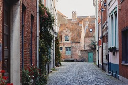 Traditional medieval architecture, narrow paved street with brick houses with red tiled roofs in town Ghent, Belgium, Europe