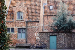 Traditional medieval architecture, old brick house with red tiled roof in town Ghent, Belgium, Europe