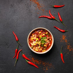 Traditional mexican dish chili con carne in ceramic bowl on black concrete background with chili peppers. Overhead view, flat lay, copy space. Minimal abstract composition