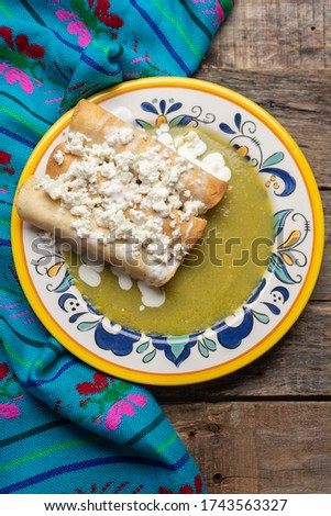 Traditional mexican drowned flautas with green sauce also called 'ahogadas' on wooden background Foto stock ©