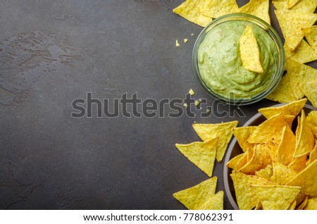 Traditional mexican homemade guacamole sauce in a glass bowl and a bowl with tortilla chips on a dark black stone background. Party food concept.  Top view, copy space, horizontal image #778062391