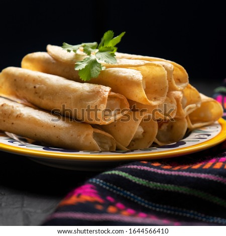 Traditional mexican potato and cheese fried tacos also called flautas on dark background Foto stock ©
