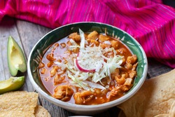 Traditional mexican red pozole soup on wooden background