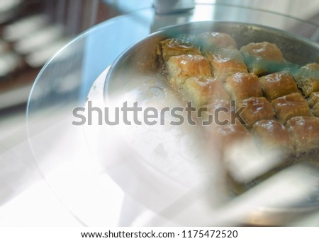 Traditional Middle Eastern sweets 'bird's nest' soaked in honey syrup with nut filling. Delicious honey dessert on a brown clay plate. Selective focus. View through the confectionery showcase Stock fotó ©