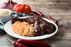 Traditional mole Poblano with rice in plate on wooden table. Copy space