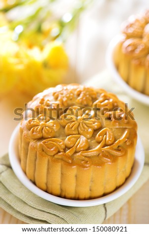 Traditional mooncakes on table setting.  Chinese mid autumn festival foods. The Chinese words on the mooncakes means assorted fruits nuts, not a logo or trademark.