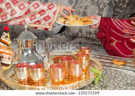 Traditional Moroccan immigrant women presenting typical Ramadan cookies and tea