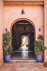 Traditional moroccan style in architecture with red terracotta wall. Arch entrance, blue lanterns and clay flower pots with plants. Perspective inside.
