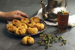 Traditional Moroccan Tea with Oriental Algerian sweet cookies( mchawak   named in arabic ), teacup and pot and mint leaves