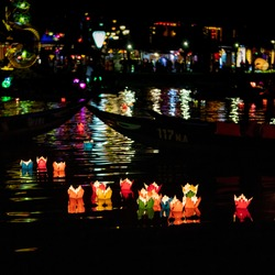 Traditional multicolored paper lanterns with candles floating down the river at night in UNESCO World Heritage Site of Ancient City Hoi An, Vietnam
