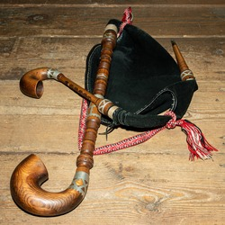 Traditional musical instrument bagpipe on wooden background.
