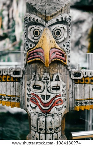Traditional national indian totem.  Totem pole sculpture art. Ancient wooden mask.  Mayan and aztecs symbolic religious gods faces.  Ethnic pagan worship and idolatry. #1064130974