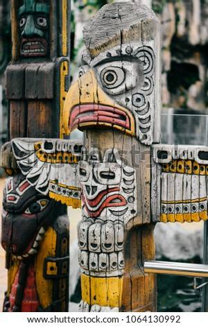 Traditional national indian totem.  Totem pole sculpture art. Ancient wooden mask.  Mayan and aztecs symbolic religious gods faces.  Ethnic pagan worship and idolatry. #1064130992