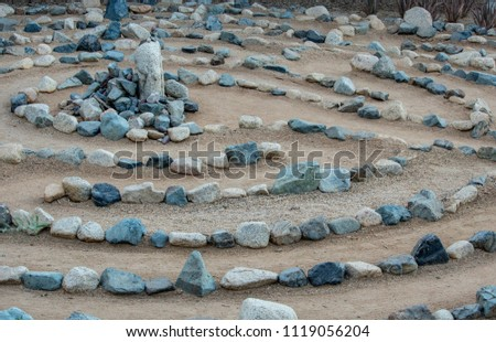 Traditional natural stone walking labyrinth maze made for contemplation and worship, created with rocks in shades of blue and turquoise.