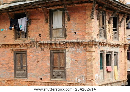 Traditional newar style red brick old house with carved wooden windowsills and roof struts-clothes hanging in the old city area. Dhulikhel-Kavrepalanchok distr.-Bagmati zone-Nepal.