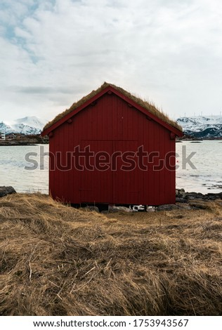 Traditional norwegian red boathouse with grassy roof - front view