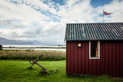 Traditional norwegian red wooden cabin in Vesteralen Islands archipelago in Northern Norway, with green grass, by the sea, an anchor and norwegian flag