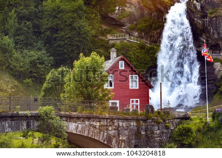traditional norwegian red wooden house and steinsdalsfossen waterfall in the background, norway