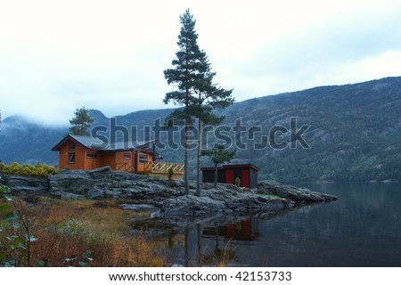 traditional norwegian wooden house standing at the lakeside and mountains in the distance