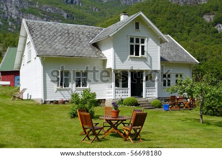 traditional norwegian wooden house standing on a lawn and mountains in the background