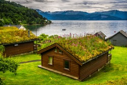 Traditional norwegian wooden house. Typical Norwegian house. Typical norwegian house with grass on the roof. Norwey