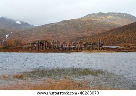 traditional norwegian wooden houses standing on a lake coast and mountains in the background