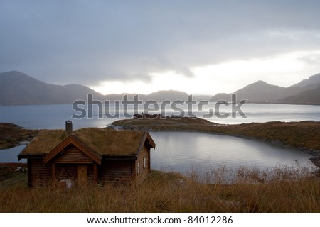 traditional norwegian wooden houses standing on a lake coast, norway
