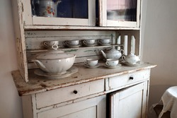 Traditional od vintage kitchen with white cupboard and porcelain bowl and cups.