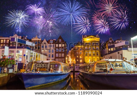 Traditional old buildings and boats with fireworks in Amsterdam, Netherlands #1189090024