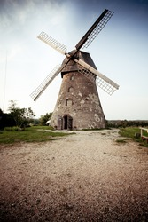 Traditional Old dutch windmill in Latvia against dark sky