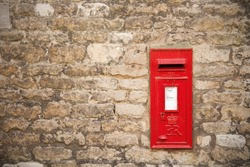 traditional old English red postbox mounted in a cotswold stone wall