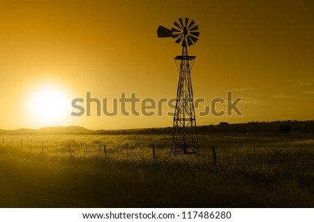 Traditional, old fashioned water pumping ranch windmill, range land, fencing. - stock photo