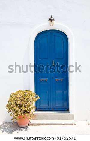 Traditional old greek blue doors in white building