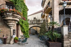 Traditional old Spanish street with beautiful balconies and arches in Barcelona town, Spain