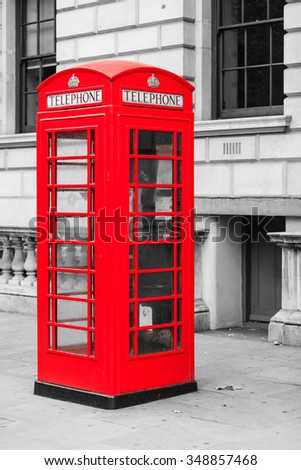 Traditional old style red telephone box, british phone booth in London England UK. Black and white street.