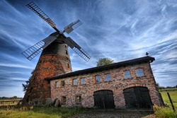 Traditional old  windmill in Germany against cloudy sky