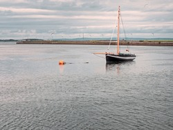 Traditional old wooden sailing boat in Galway bay. Black hull and orange mast, classic color.