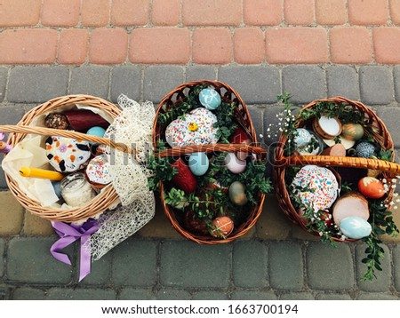 Traditional orthodox Easter food for blessing. Easter baskets with stylish painted eggs, easter cake, ham,beets, butter, candle with boxwood branches for sanctify at church. Stockfoto ©