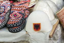 Traditional Ottoman market in Kruja, birth town of National Hero Skanderbeg. Flea market in Albania. Wool craft souvenirs for sale. Traditional Albanian male headdress on foreground.