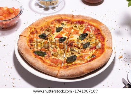Traditional pan dough pizza of mozzarella cheese with chopped tomatoes, pitted green olives and basil leaf on the white table Stock fotó ©