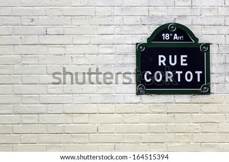 Traditional Paris plaque with the name of the street on white brick wall