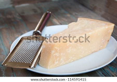 Traditional parmesan cheese on a white plate with a hand grater on a rustic wooden tabletop.