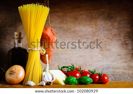Traditional pasta cooking ingredients on a wooden background with text copy space