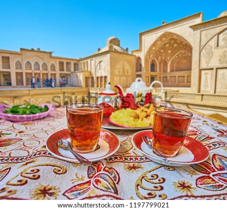 Traditional persian restaurant offers tasty tea with local sweets on the tray - candies of rock sugar and almond pancakes, Kashan, Iran. #1197799021
