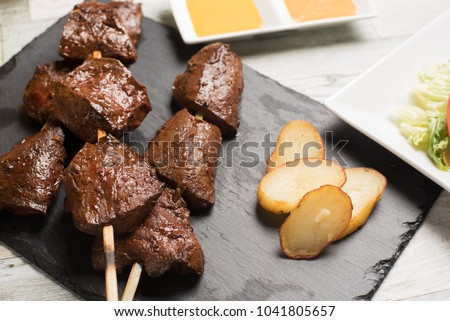 Traditional Peruvian food called anticuchos grilled skewered beef heart meat with boiled potato and white corn