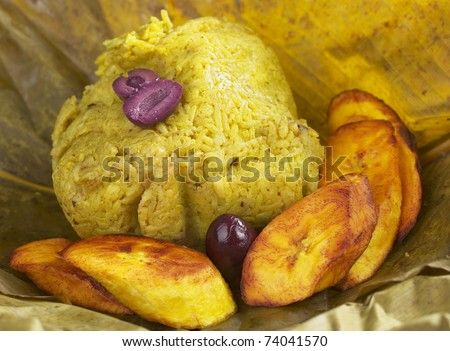 Traditional Peruvian food called Juane from the jungle area. This meal consists of rice, meat, eggs and black olives and is wrapped in bijao leave. It's accompanied by fried plantains and black olives