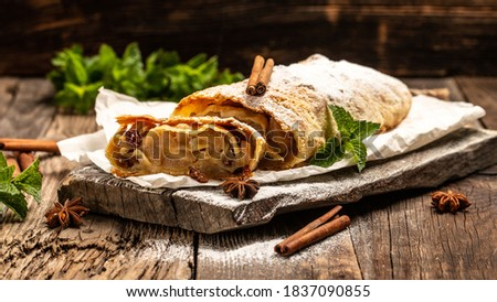 Photo of  Traditional pieces of apple strudel with cinnamon, raisin, powdered sugar and mint. classic and probably the best known Viennese pastry outside of Austria.