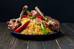 Traditional Pilaf With Loin Chops Lamb On Plate On Wooden Table, Black Background. Side View.