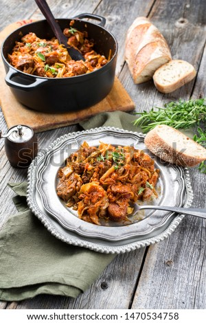 Traditional Polish kraut stew bigos with sausage, meat and mushrooms as top view in a cast iron pot and pewter plate on an old rustic board  #1470534758