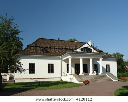 Traditional Polish style manor house with white walls and wooden shingle roof